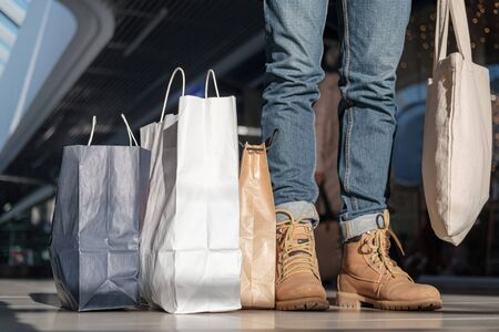 A busy shopper, concept of consumerism and hunting for sales items. A person stands with sustainable paper and canvas bags at the shopping mall