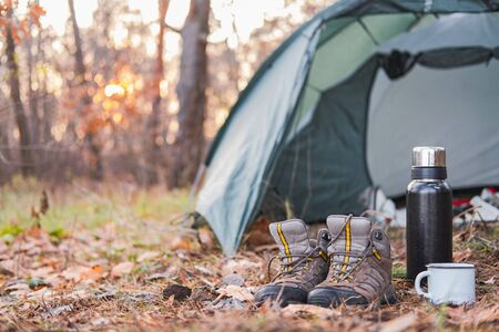 Active rest outdoors: hiking shoes and hot drink at a camping place. Camping place scene: trekking acessories stand by the tent in the forest