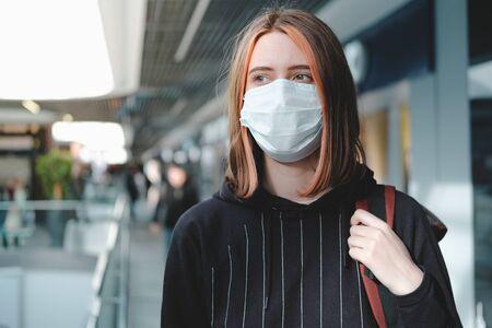 Woman in a protective face mask at public place. Coronavirus, COVID-19 spread prevention concept, responsible social behaviour of a citizen Stock Photo
