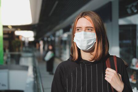 Woman in a protective face mask at a shopping mall. Coronavirus, COVID-19 spread prevention concept, responsible social behaviour of a citizen Stock Photo