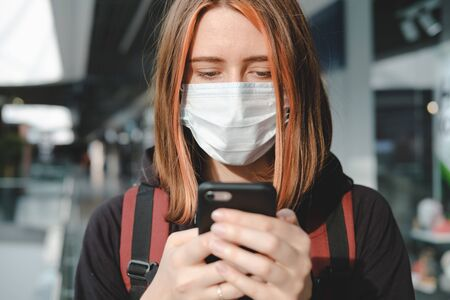 Woman in protective face mask using the phone at a public place. Coronavirus, COVID-19 spread prevention concept, responsible social behaviour of a citizen Stock Photo