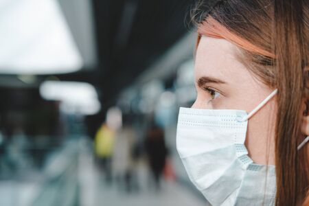 Porrait of a female person with face mask at a public place. Coronavirus, COVID-19 spread prevention concept, responsible social behaviour of a citizen Stock Photo