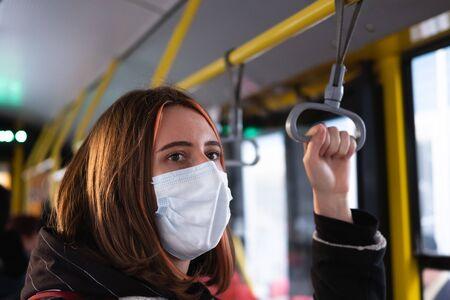 Female commuter wears a protective mask in public transport. Coronavirus, COVID-19 spread prevention concept, responsible social behaviour of a citizen Stock Photo