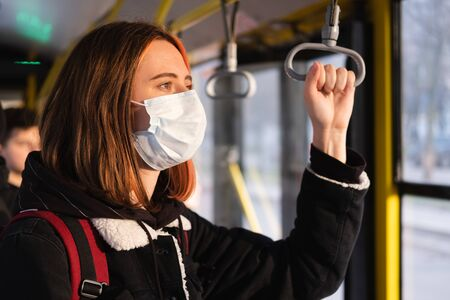 Woman in a protective mask on the train or on the bus. Coronavirus, COVID-19 spread prevention concept, responsible social behaviour of a citizen