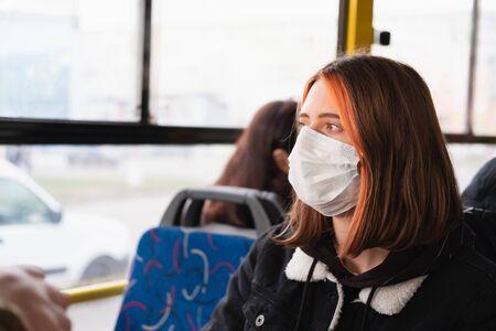 Woman commutes in a protective face mask. Coronavirus, COVID-19 spread prevention concept, responsible social behaviour of a citizen Stock Photo