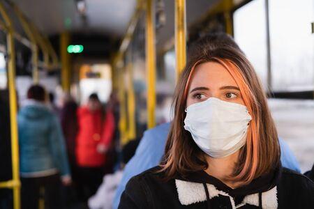 Junge weibliche Erwachsene pendelt in einer schützenden Gesichtsmaske. Coronavirus, COVID-19-Verbreitungspräventionskonzept, verantwortungsbewusstes Sozialverhalten eines Bürgers Standard-Bild