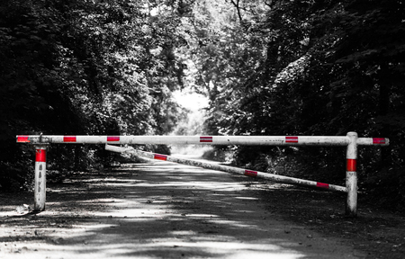 a barrier crossing a way in the forest; crossbar is isolated from the desaturated background Stock Photo