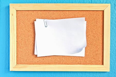 notepad on cork board on sky-blue background photo