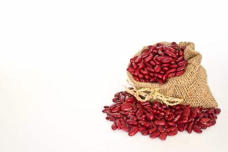 Red beans in canvas sack on white background photo