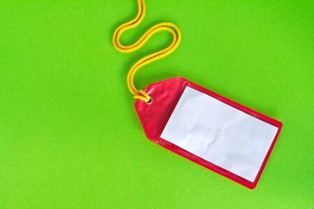 Rad plastic luggage tag isolated on green background  photo