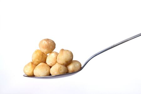 Spoonful of macadamia nuts on white background