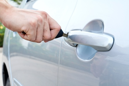 A hand opening a car door with a key
