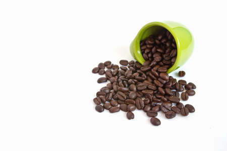 Coffee beans in green cup on white background photo