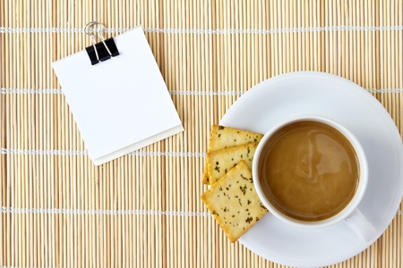 White cup of hot coffee and white sketch book on a mat