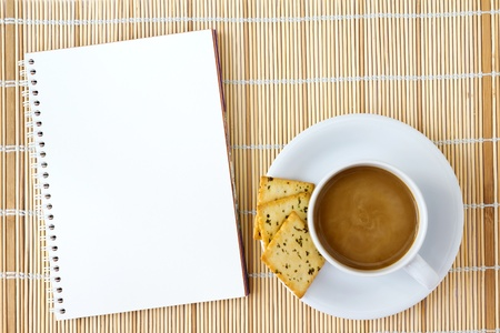 White cup of hot coffee and white sketch book on a mat  photo