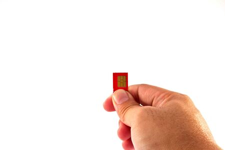 Fingers holding a mobile phone GSM SIM Card. Isolated on white background  Stock Photo