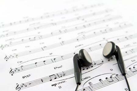 lows: An ear phone on the top of a music sheet
