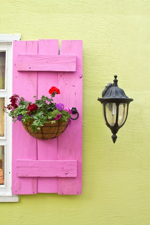 mediterranean houses: Pink window on the green wall with Lamp. Stock Photo