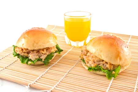 Two fresh burger with tuna on a mat and orange juice Stock Photo