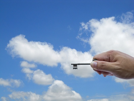 trenching: hand holding keys  on sky background