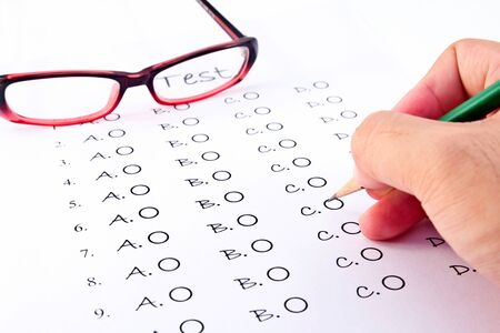Hand on pencil choosing the test list and glasses on the examination  photo