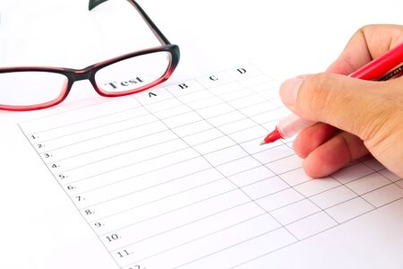 Hand on red pen choosing the test list and glasses on the examination  photo