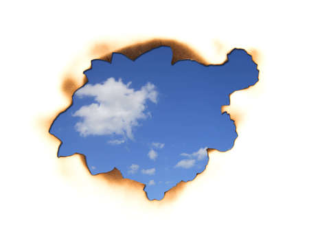 Burnt hole in a paper over sky background  Stock Photo - 12832031
