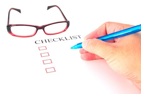 Checklist with pen, glasses and checked boxes.  photo