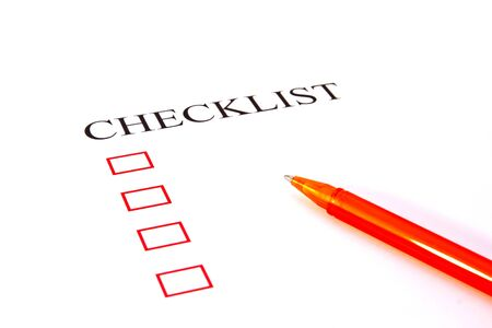 Checklist with pen and checked boxes.  photo