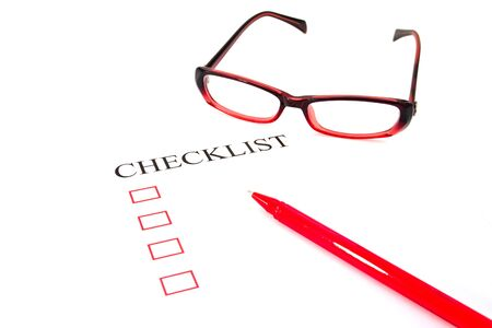 Checklist with pen, glasses and checked boxes