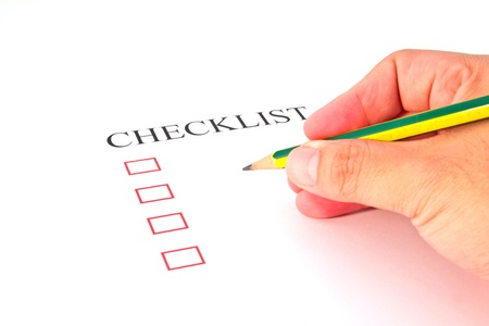 Checklist with pencil and checked boxes.  photo