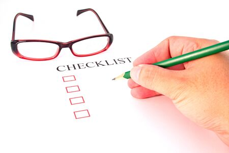 Checklist with pencil, glasses and checked boxes