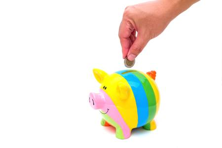 Hand with coin over a piggy bank on white background with reflection Stock Photo - 14321159