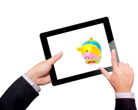 Businessman hands are holding the contemporary digital tablet with piggy bank style money box  Concept image on cloud-computing theme  Isolated on white Stock Photo - 16582541