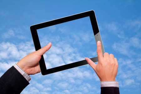 Hands with tablet computer. Isolated sky