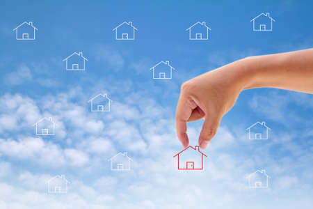 Hand select home symbol on blue sky photo