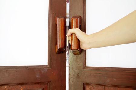 tocar la puerta: Sostenga la manija de la puerta de madera Foto de archivo