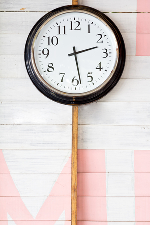 Clock on color wooden plank wall photo