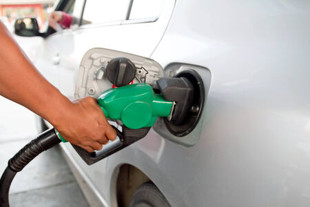 close up of man hand putting gas into the car at gas station photo