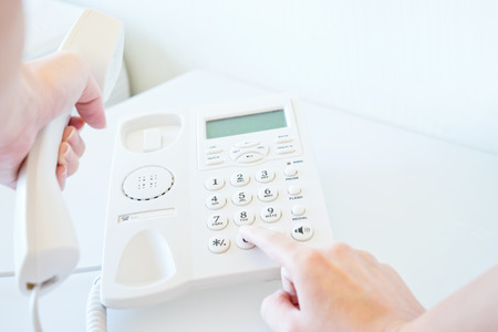 Photo of female hands dialing on white telephone Stock Photo