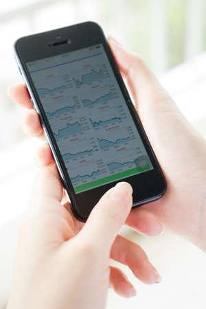 Women analyse stock market using mobile smart phone