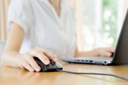 rat�n: Image of female hands clicking computer mouse Foto de archivo