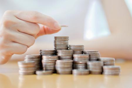 dinero euros: La mano puso la moneda a la pila de monedas en el fondo blanco