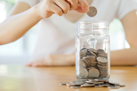 money jar: Woman hands with coins in glass jar, close up Stock Photo