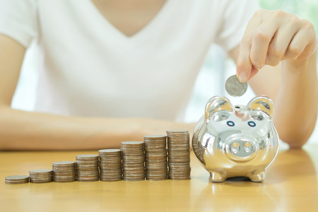 putting money in pocket: saving money-young woman putting a coin into a money-box-close up Stock Photo