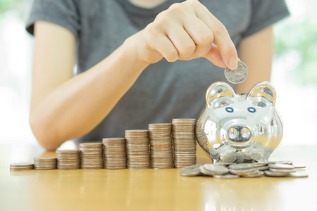 saving money-young woman putting a coin into a money-box-close up Stock Photo