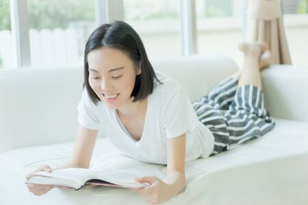 25 30 years: Woman reading a book on a sofa Stock Photo