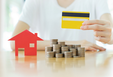 card house: Real estate investment by credit card. House and coins on table. Stock Photo