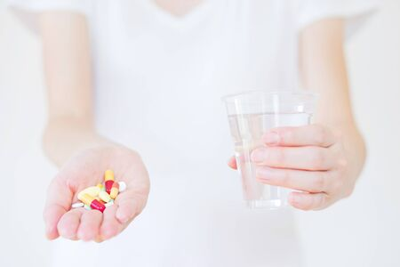 vitamin pill: Hands with pills and glass of water isolated on white Stock Photo