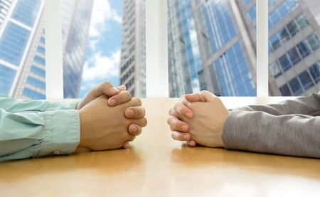 clasped: Negotiation of two businessman with clasped hands in office.